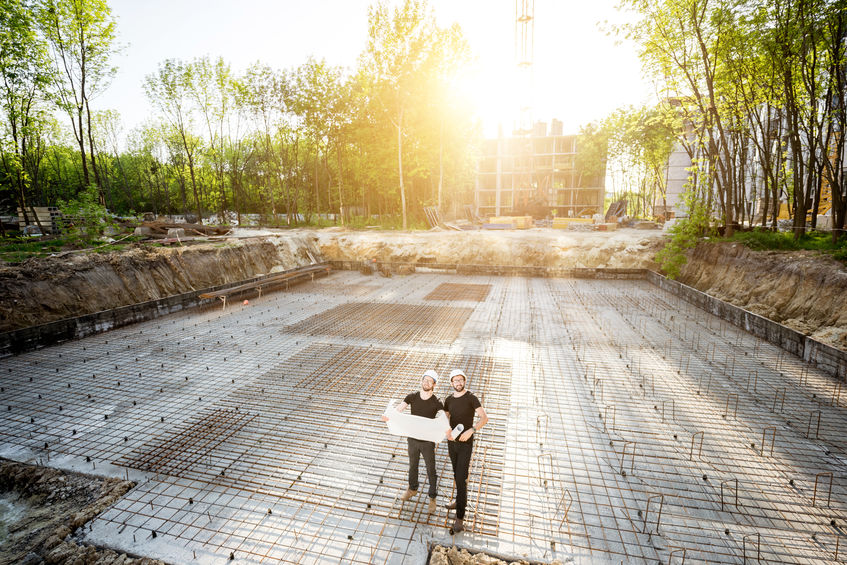 Wide angle view on the concrete foundation at the construction site with two builders standing with drawings during the sunset