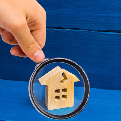 Magnifying glass is looking at the wooden house with a crack. The concept of a damaged house, dilapidated housing. Renovation, repair and restoration of the old building. Property insurance.
